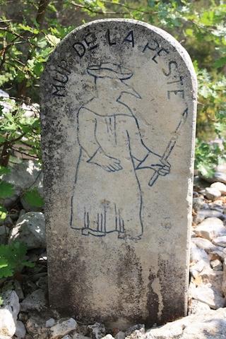 Markeringsteen met afbeelding van een pestdokter bij de Mur de la Peste in de Provence. Deze muur was gebouwd om de pest tegen te houden vanuit Marseille en omgeving